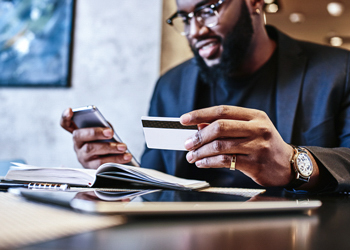 Shot of african american businessman holding mobile and credit c